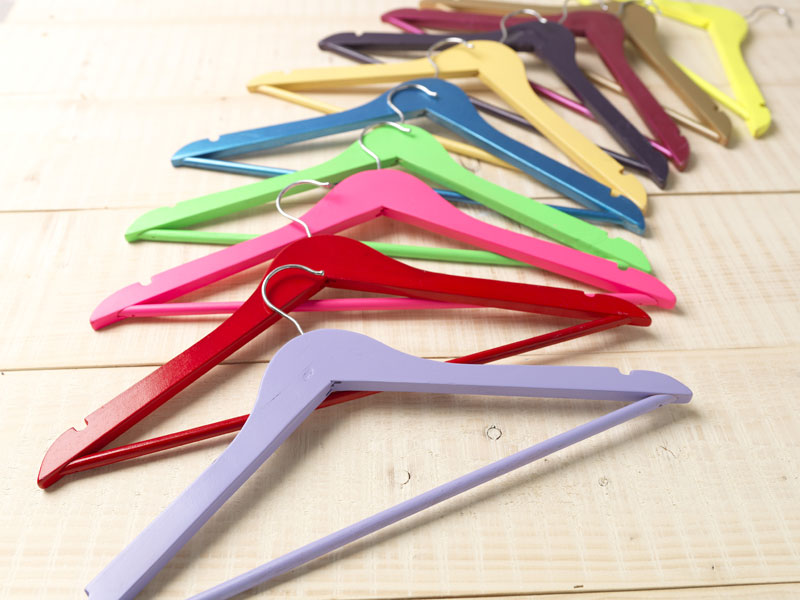 Colorful-Wooden-Coat-Hangers-Spread-Out-On-Wooden-Floor